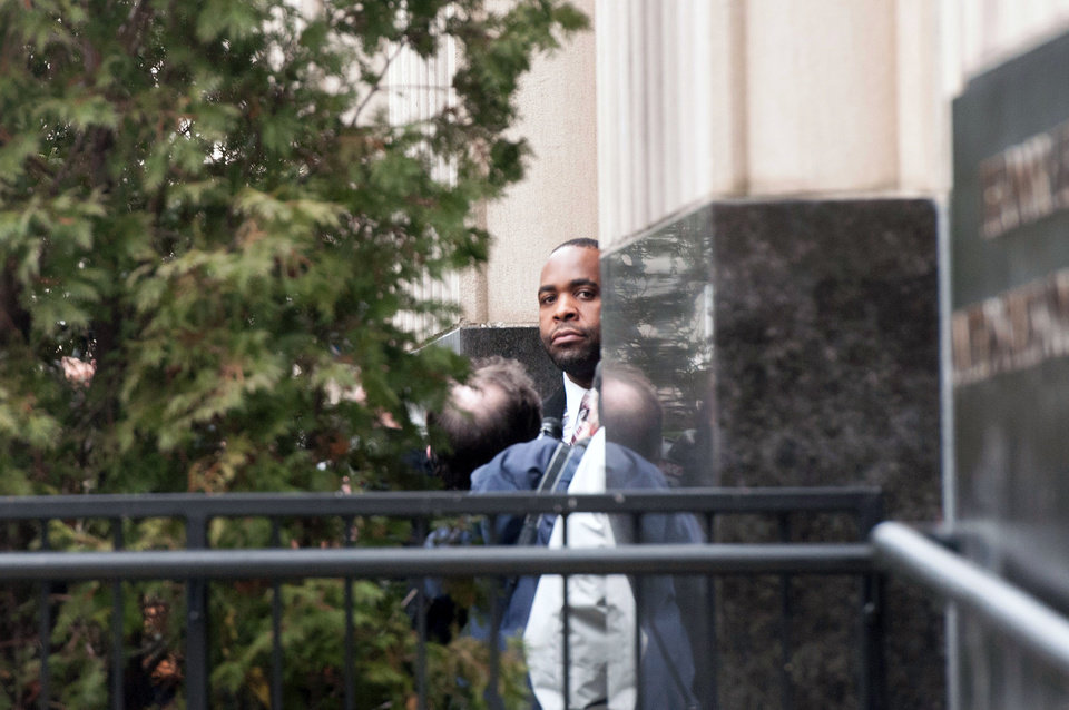 Photo - Ex- Detroit Mayor Kwame Kilpatrick peers out from the Theodore Levin Federal U.S. Courthouse in Detroit following his 6-month-long corruption trial  in which Kilpatrick was found guilty on 24 of 30 counts, including racketeering and extortion convictions on Monday, March, 11, 2013. Kilpatrick's long-time contractor friend, Bobby Ferguson was found guilty of 9 of 11 racketeering and extortion counts. Kwame Kilpatrick's father, Bernard Kilpatrick was convicted of 1 of 4 counts including filing a false tax return. (AP Photo/AnnArbor.com, Tanya Moutzalias)