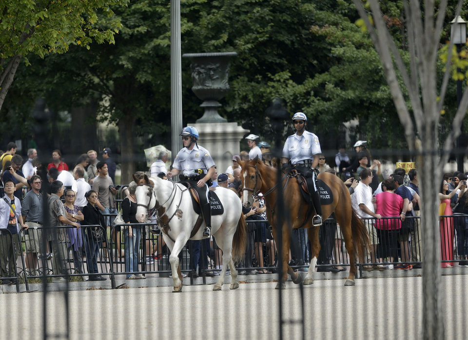 Photo - US Park Police police on horseback patrol assist Secret Service during a shutdown Pennsylvania Ave., directly in front of the White House in Washington, Thursday, Oct. 3, 2013, after reports of shots on Capitol Hill. (AP Photo/Pablo Martinez Monsivais) ORG XMIT: DCPM102