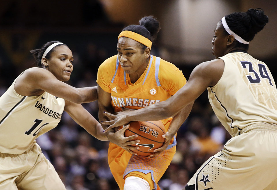 Photo - Tennessee guard Ariel Massengale, center, drives between Vanderbilt's Christina Foggie (10) and Tiffany Clarke (34) during the first half of an NCAA college basketball game, Thursday, Jan. 24, 2013, in Nashville, Tenn. (AP Photo/Mark Humphrey)