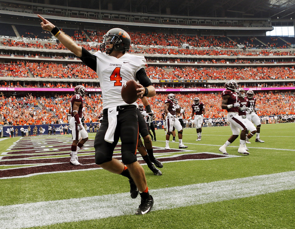 Oklahoma State's J.W. Walsh (4) celebrates a touchdown run in the second quarter during the AdvoCare Texas Kickoff college football game between the Oklahoma State University Cowboys (OSU) and the Mississippi State University Bulldogs (MSU) at Reliant Stadium in Houston, Saturday, Aug. 31, 2013. Photo by Nate Billings, The Oklahoman