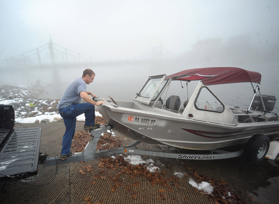 Photo - Scott Moser, of Palmer Township, Pa., puts his boat in the Delaware River from the boat launch in Phillipsburg, N.J. to run the motor as heavy fog surrounds the area on Sunday, Dec. 22, 2013. (AP Photo/The Express-Times, Matt Smith)