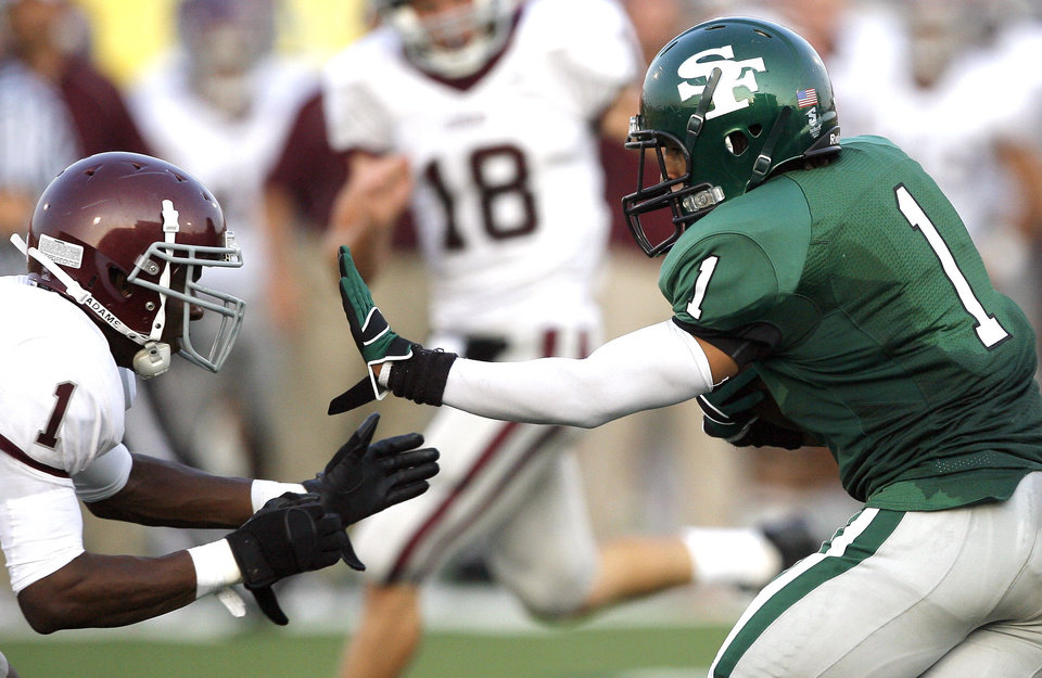 Photo - Edmond Santa Fe's Phillip Sumpter tries to get by Edmond Memorial's Ashton Antwine during the high school football game between Edmond Santa Fe and Edmond Memorial at Wantland Stadium in Edmond, Okla.,  Friday, Sept. 2, 2011. Photo by Sarah Phipps, The Oklahoman