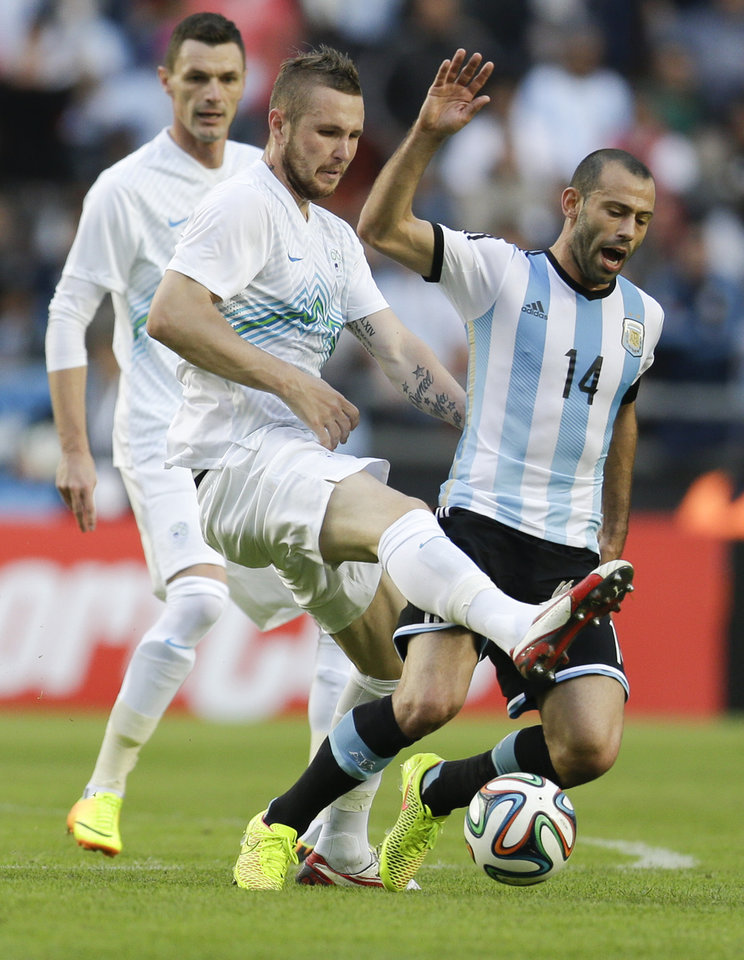 Photo - Argentina's Javier Mascherano, right, fights for the ball with Slovenia's Jasmin Kurtic during their international friendly soccer match in La Plata, Argentina, Saturday, June 7, 2014. Argentina's team is leaving June 9 for Brazil to compete in the World Cup. (AP Photo/Natacha Pisarenko)