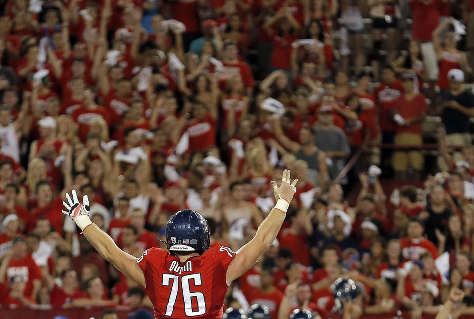 Photo - Arizona's Kyle Quinn (76) celebrates a win over OSU following the college football game between the University  of Arizona and Oklahoma State University at Arizona Stadium in Tucson, Ariz.,  Sunday, Sept. 9, 2012. Photo by Sarah Phipps, The Oklahoman