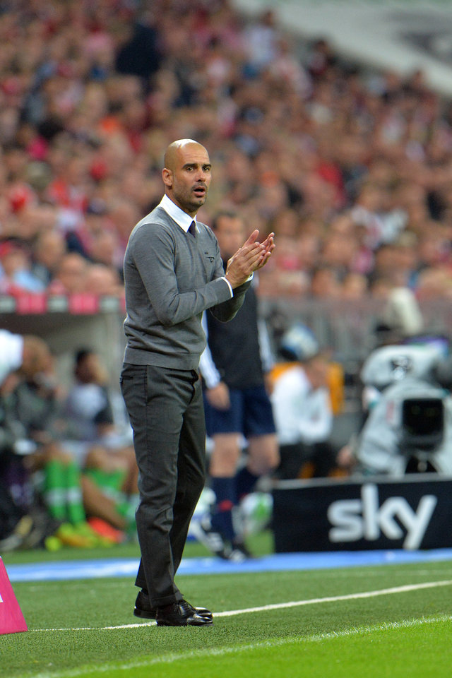 Photo - Munich head coach Pep Guardiola reacts during the  soccer match between FC Bayern Munich and VfL Wolfsburg in the Allianz Arena in Munich, Germany, on Friday, Aug. 22, 2014. (AP Photo/Kerstin Joensson)