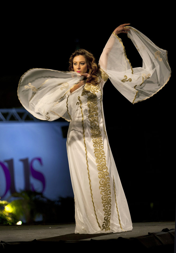 Photo - In this photo taken Friday, May 2, 2014, a model displays a creation by designer Intisar Abdo during the second day of the Palestine Fashion Week 2014, in the West Bank city of Ramallah. The collections showed a blend of traditional Palestinian embroidery and modern designs. (AP Photo/Nasser Nasser)