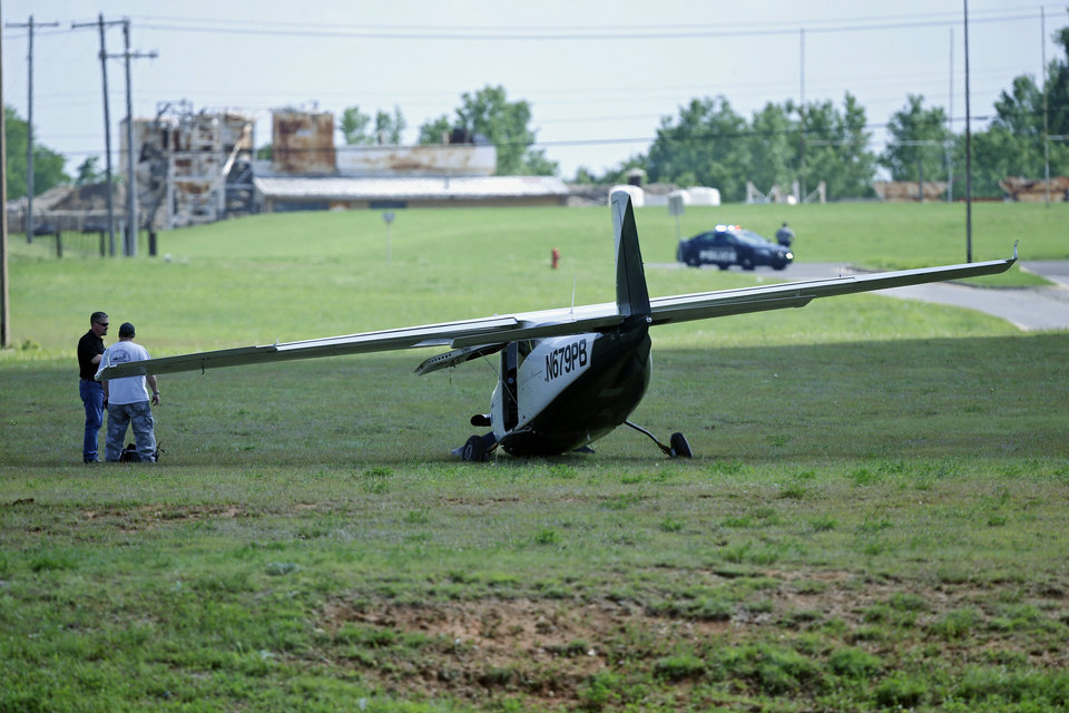 Photo - Two people stand at a small plane that made an emergency landing in a field Monday, May 6, 2019, in Oklahoma City. Oklahoma City firefighters say the pilot of the small plane made an emergency landing along a roadway when the aircraft had mechanical problems heading to an airport. (AP Photo/Sue Ogrocki)