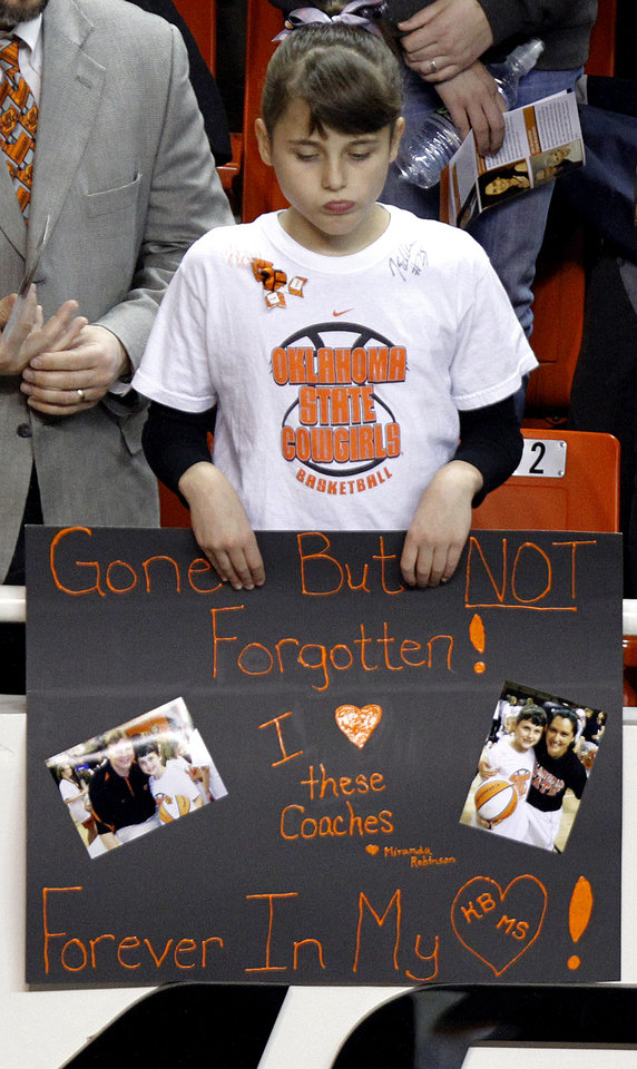 Photo - An Oklahoma State fan shows her support with a banner during the memorial service for Oklahoma State head basketball coach Kurt Budke and assistant coach Miranda Serna at Gallagher-Iba Arena on Monday, Nov. 21, 2011 in Stillwater, Okla. The two were killed in a plane crash along with former state senator Olin Branstetter and his wife Paula while on a recruiting trip in central Arkansas last Thursday. Photo by Chris Landsberger, The Oklahoman
