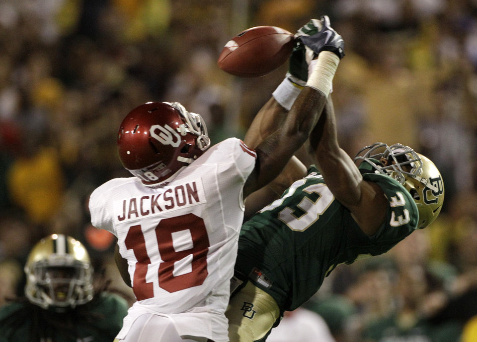 Photo - Oklahoma wide receiver Kameel Jackson (18) prevents Baylor safety Josh Wilson (33) from making an interception on a tipped ball in the first half of an NCAA college football game Saturday, Nov. 19, 2011, in Waco, Texas. (AP Photo/Tony Gutierrez)