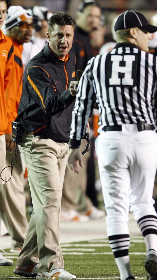 Photo - Head coach Mike Gundy talks with a referee during the second half of the college football game between the Oklahoma State University Cowboys (OSU) and the Texas Tech Red Raiders at Jones AT&T Stadium on Saturday, Nov. 8, 2008, in Lubbock, Tex.  Texas tech won 56-20.By Steve Sisney/The Oklahoman