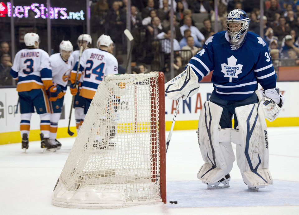 Toronto Maple Leafs goaltender James Reimer looks at the puck as the New York Islanders celebrate a goal by John Tavares during the first period of their NHL hockey game in Toronto, Thursday, April 18, 2013. (AP Photo/The Canadian Press, Frank Gunn)
