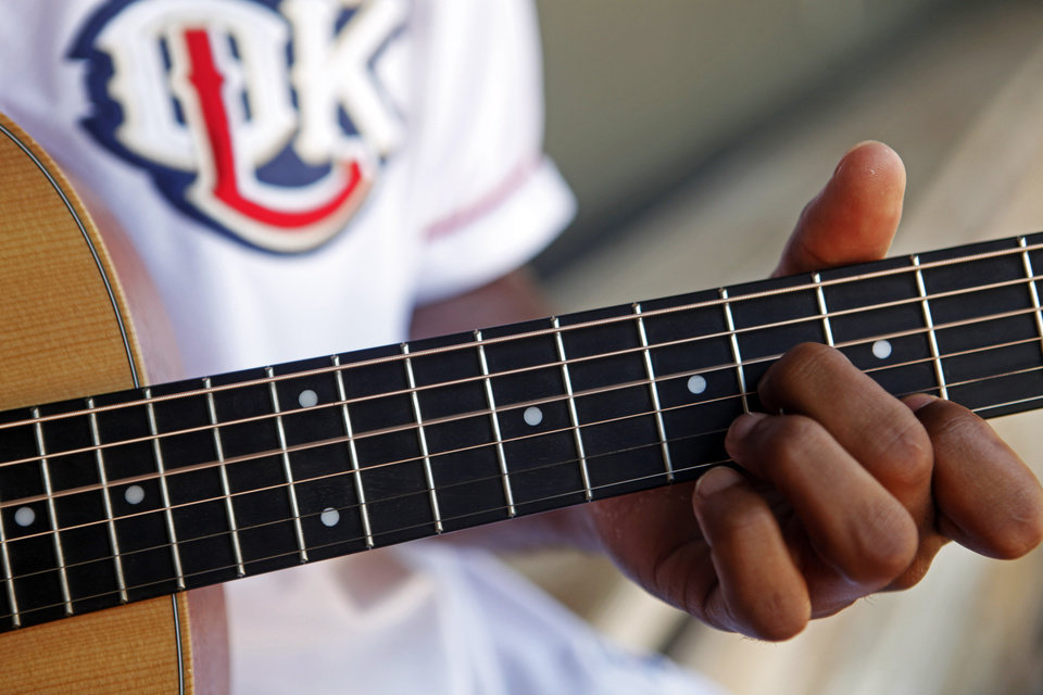 Photo - Redhawks outfielder Austin Wates plays his guitar in the dugout before practice at the Chickasaw Bricktown Ballpark in Oklahoma City on July 8, 2014. Wates taught himself to play guitar from YouTube videos while on the road with the team. Photo by KT King/The Oklahoman