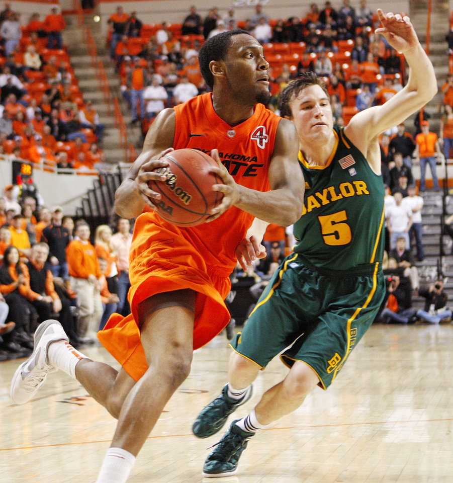 Photo - OSU's Brian Williams (4) takes the ball past Baylor's Brady Heslip (5) in the second half of a men's college basketball game between the Oklahoma State University Cowboys and the Baylor University Bears at Gallagher-Iba Arena in Stillwater, Okla., Saturday, Feb. 4, 2012. Baylor beat OSU, 64-60. Photo by Nate Billings, The Oklahoman