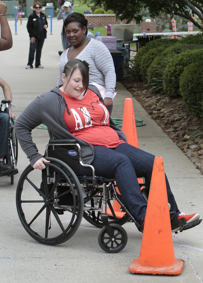 Photo - University of Central Oklahoma sophomore Stephanie Smith navigates a wheelchair through obstacles.
