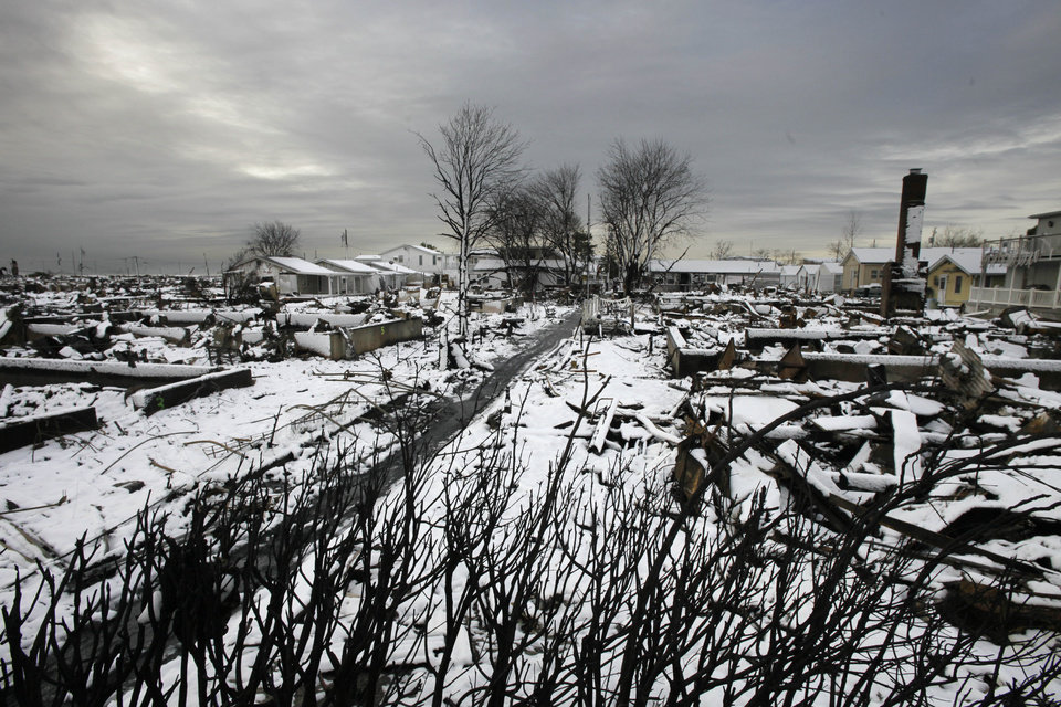 Photo - The fire-scorched landscape of Breezy Point is shown after a Nor'easter snow, Thursday, Nov. 8, 2012 in New York.  The beachfront neighborhood was devastated during Superstorm Sandy when a fire pushed by the raging winds destroyed many homes.  (AP Photo/Mark Lennihan) ORG XMIT: NYML104