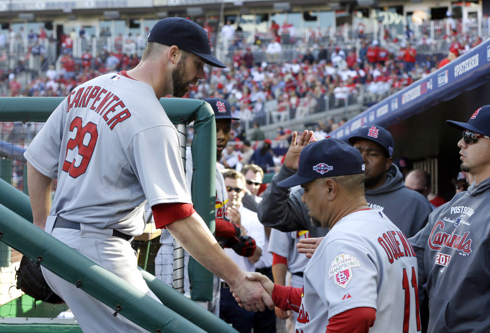 Photo -   St. Louis Cardinals starting pitcher Chris Carpenter, left, is greeted by third base coach Jose Oquendo and teammates in the dugout after being relieved in the sixth inning of Game 3 of the National League division baseball series against the Washington Nationals on Wednesday, Oct. 10, 2012, in Washington. (AP Photo/Pablo Martinez Monsivais)