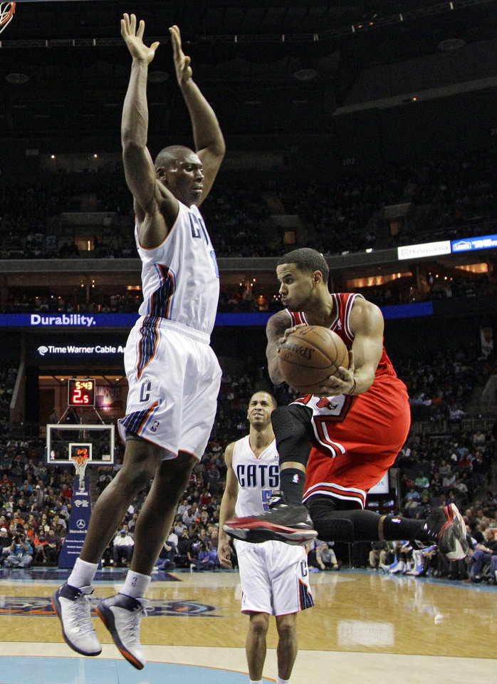 Photo - Chicago Bulls' D.J. Augustin, right, looks to pass around Charlotte Bobcats' Bismack Biyombo, left, during the first half of an NBA basketball game in Charlotte, N.C., Saturday, Jan. 25, 2014. (AP Photo/Chuck Burton)