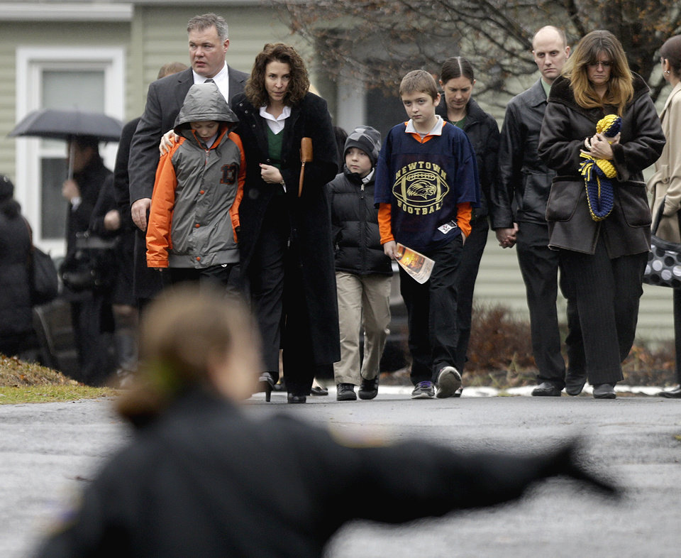 Photo - Mourners leave the funeral service of Sandy Hook Elementary School shooting victim, Jack Pinto, 6, Monday, Dec. 17, 2012, in Newtown, Conn. Pinto was killed when a gunman walked into Sandy Hook Elementary School in Newtown Friday and opened fire, killing 26 people, including 20 children.(AP Photo/David Goldman) ORG XMIT: CTDG118