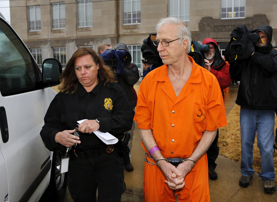 Photo - Gary Doby  is taken from the  Pottawatomie County Courthouse Wednesday afternoon, Jan. 9, 2013, after the former Oklahoma Baptist University professor  pleaded guilty  to 20 charges of sex crimes against children and was sentenced to life in prison. He must serve more than 38 years before becoming eligible for parole. Prosecutors charged Doby and Kimberly Crain, a  former teacher at McLoud Elementary School, with sex crimes for allegedly photographing some of her female students in skimpy clothing and underwear.     Photo by Jim Beckel, The Oklahoman
