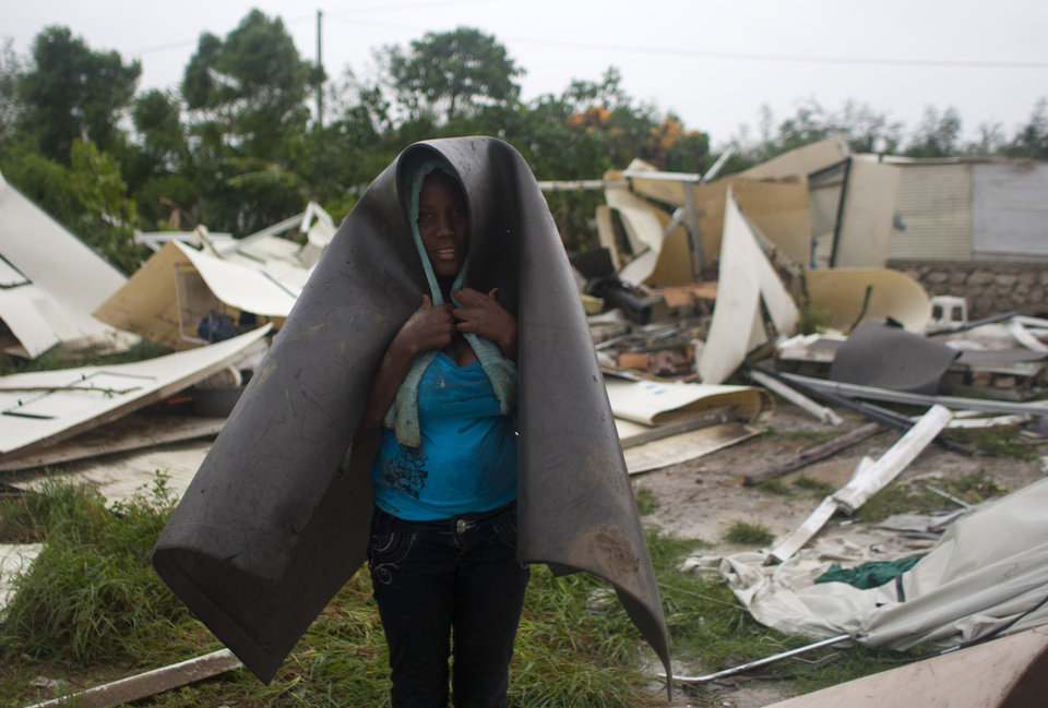 Photo -   A woman covers herself with what's left of her home in a camp set up for people displaced by the 2010 earthquake that was destroyed by Tropical Storm Isaac in Port-au-Prince, Haiti, Saturday Aug. 25, 2012. Tropical Storm Isaac swept across Haiti's southern peninsula early Saturday, dousing a capital city prone to flooding and adding to the misery of a poor nation still trying to recover from the 2010 earthquake. (AP Photo/Dieu Nalio Chery)