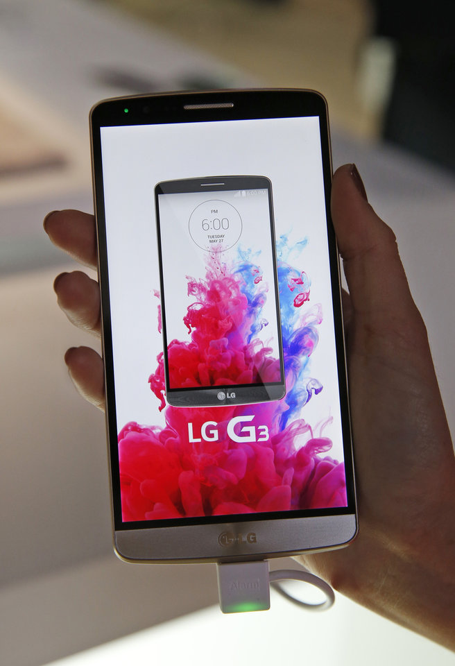 Photo - An LG employee holds the company's newly unveiled smartphone called the G3 at a press event in London, Tuesday, May 27, 2014. (AP Photo/Lefteris Pitarakis)
