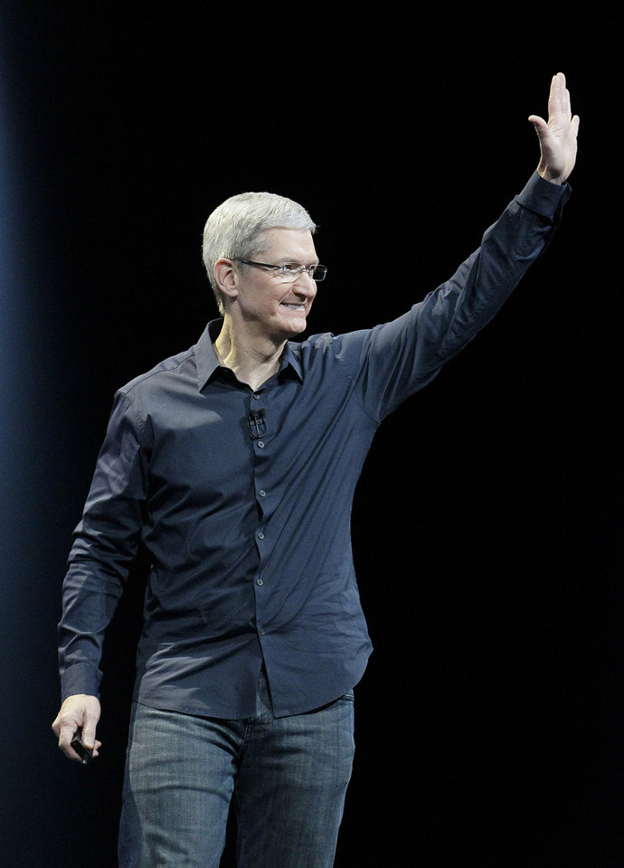 Photo - Apple CEO Tim Cook waves at the Apple Worldwide Developers Conference event in San Francisco, Monday, June 2, 2014. (AP Photo/Jeff Chiu)