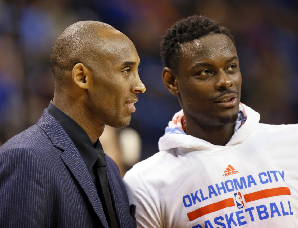 Photo - Los Angeles' Kobe Bryant (24), left, talks to Oklahoma City's Anthony Morrow (2) as the teams warm up for the second half during an NBA basketball game between the Oklahoma City Thunder and the Los Angeles Lakers at Chesapeake Energy Arena in Oklahoma City, Saturday, Dec. 19, 2015. Oklahoma City won 118-78. Bryant did not play because of a sore right shoulder. Photo by Nate Billings, The Oklahoman