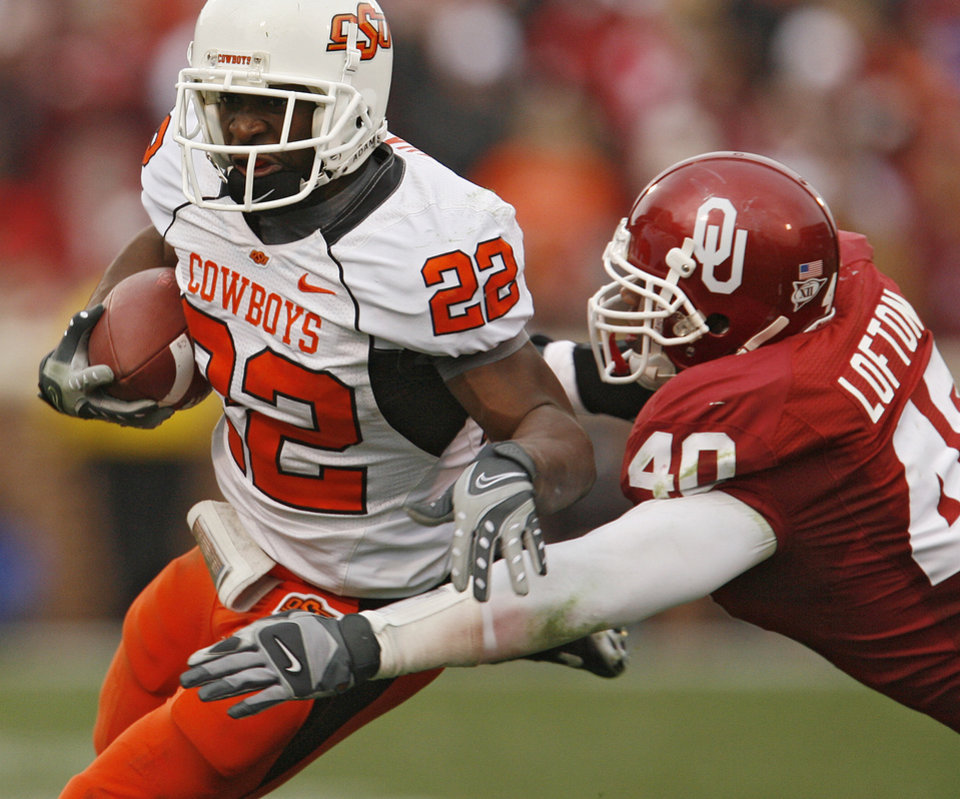 Photo - Oklahoma State's Dantrell Savage (22) gets past Oklahoma's Curtis Lofton (40) during the first half of the college football game between the University of Oklahoma Sooners (OU) and the Oklahoma State University Cowboys (OSU) at the Gaylord Family-Memorial Stadium on Saturday, Nov. 24, 2007, in Norman, Okla.  Photo By Bryan Terry, The Oklahoman