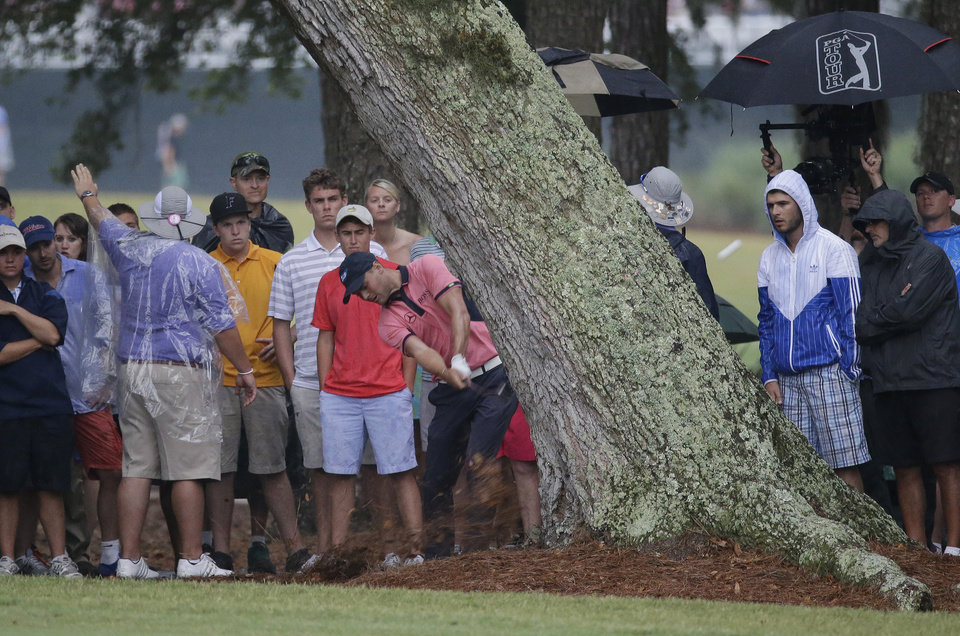Photo - Martin Kaymer of Germany, hits from behind a tree off the 15th fairway during the final round of The Players championship golf tournament at TPC Sawgrass, Sunday, May 11, 2014 in Ponte Vedra Beach, Fla. Kaymer made double bogey on the hole but went on to win the championship. (AP Photo/John Raoux)