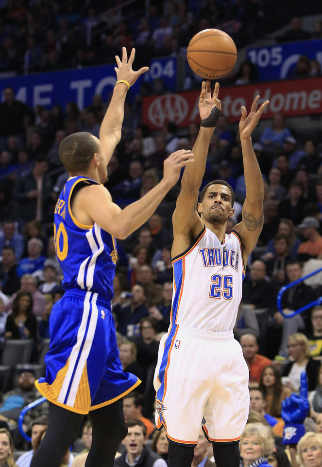 Photo - Oklahoma City Thunder shooting guard Thabo Sefolosha (25) shoots over Golden State Warriors point guard Stephen Curry (30) during the third quarter of an NBA basketball game Friday, Jan. 17, 2014, in Oklahoma City. (AP Photo/Alonzo Adams)