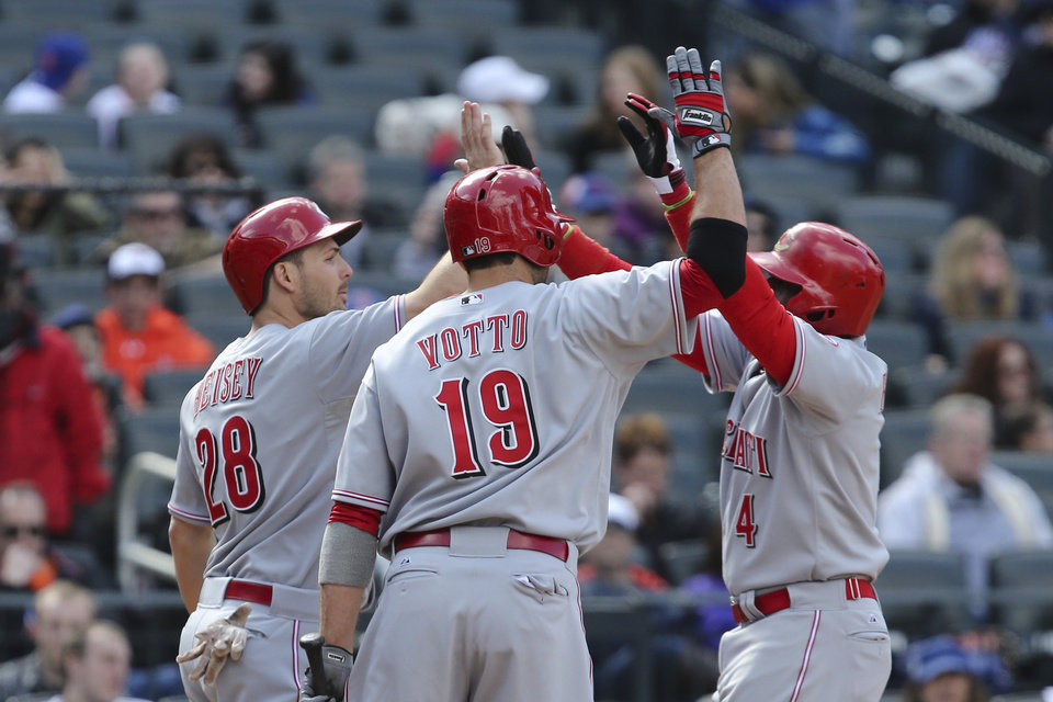 Photo - Cincinnati Reds second baseman Brandon Phillips (4) celebrates with left fielder Chris Heisey (28) and first baseman Joey Votto (19) after hitting a two-run home run in the seventh inning of their baseball game against the New York Mets at Citi Field, Saturday, April 5, 2014, in New York. (AP Photo/John Minchillo)
