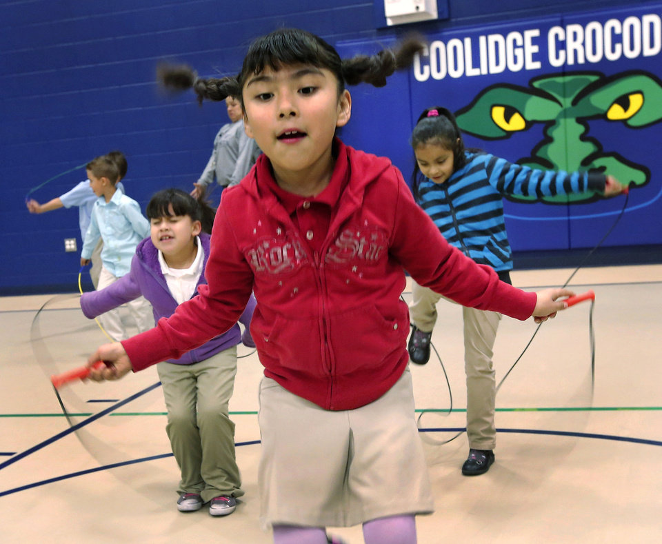 Photo - Second-grader Yamilet Soliz jumps rope with fellow students during P.E. class at Coolidge Elementary School in southwest Oklahoma City.  Jim Beckel - THE OKLAHOMAN
