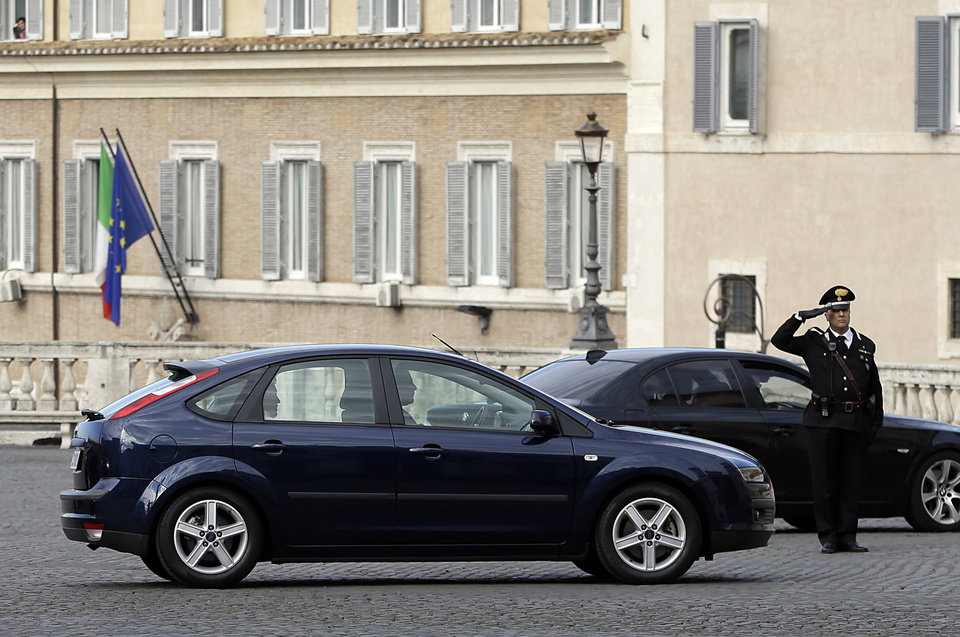 Photo - Pope Francis, sitting in the back seat of acar, arrives at the Qurinale Presidential palace to meet with Italian President Giorgio Napolitano, in Rome, Thursday, Nov. 14, 2013. Pope Francis has traveled across town for his first state visit with the Italian president, a traditionally pomp-filled ceremony that the simple pontiff defused by declining a presidential guard escort and taking his own Ford Focus instead. Francis' small motorcade pulled up quietly Thursday to the Quriniale Palace without the blaring of sirens that typically accompanies diplomats and politicians cruising through central Rome. (AP Photo/Gregorio Borgia)