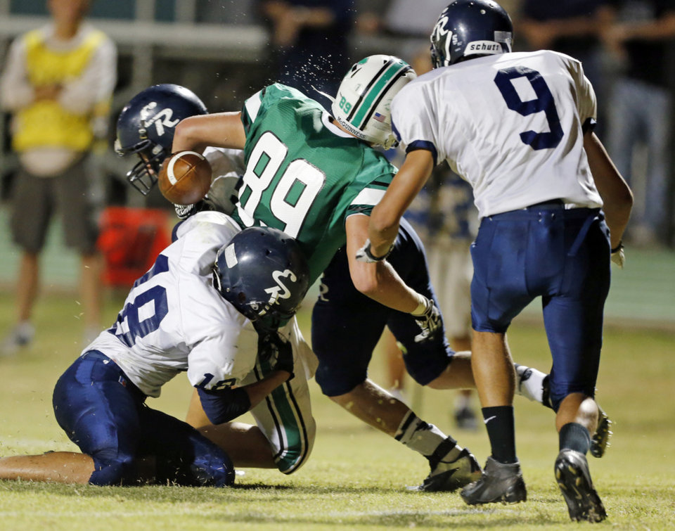 El Reno's Josh Robinson, behind, jars the ball lose from McGuinness' David Love as the Indians play the Bishop McGuinness Fighting Irish in high school football on Friday, Sept. 21, 2012 in Oklahoma City, Okla.  McGuinness recovered the ball.  Photo by Steve Sisney, The Oklahoman