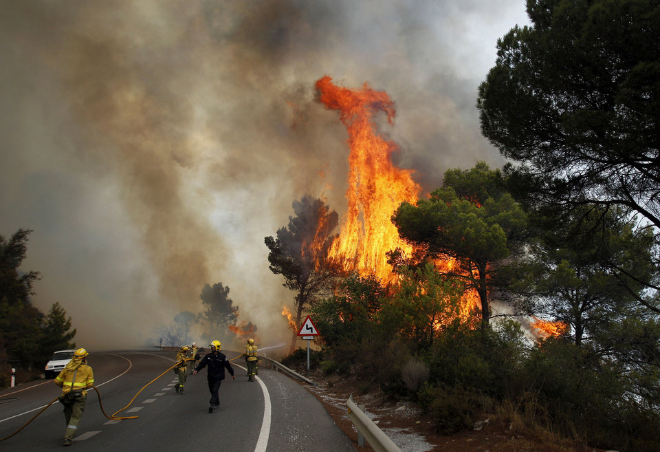 Photo -   Firefighters work to control a raging forest fire as trees are engulfed in flames next to a road in Ojen, southern Spain, Friday, Aug. 31, 2012. Spanish officials say some 4,000 people have been evacuated from their houses as a wildfire abetted by strong winds spread rapidly through hills around the popular southern tourist city of Marbella. (AP Photo/Sergio Torres)