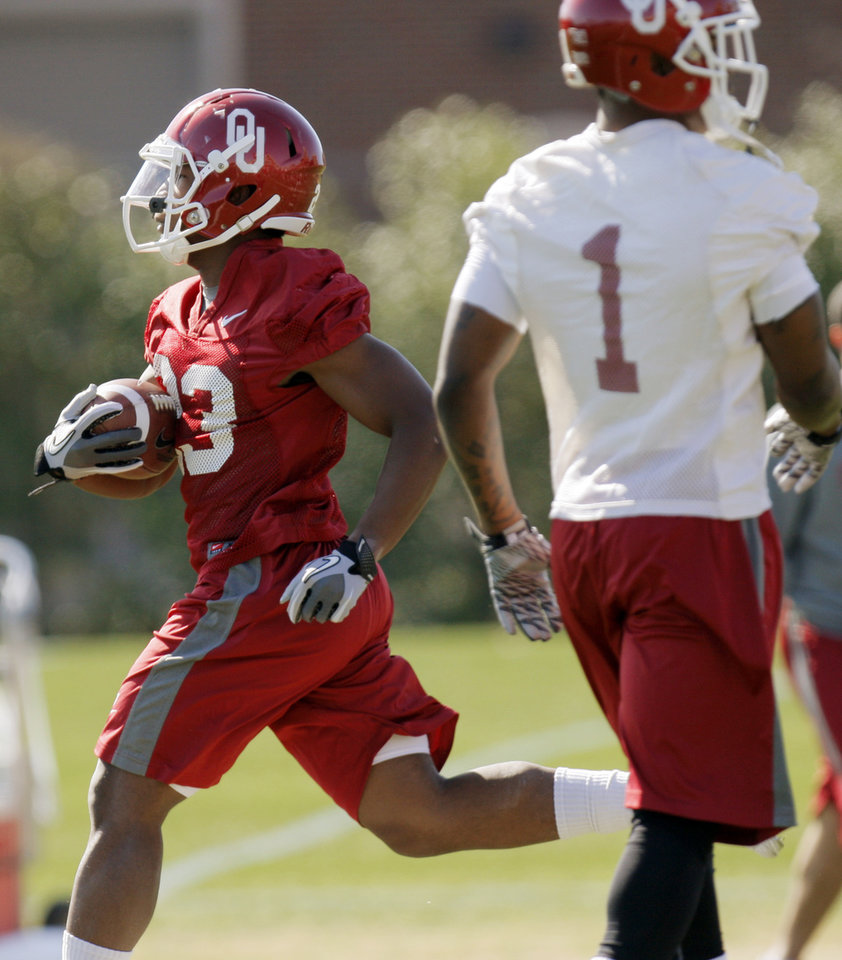 Photo - COLLEGE FOOTBALL: Danzel Williams (23) carries the ball near Tony Jefferson (1) during spring football practice for the OU Sooners on the campus of the University of Oklahoma in Norman, Okla., Monday, March 5, 2012. Photo by Nate Billings, The Oklahoman