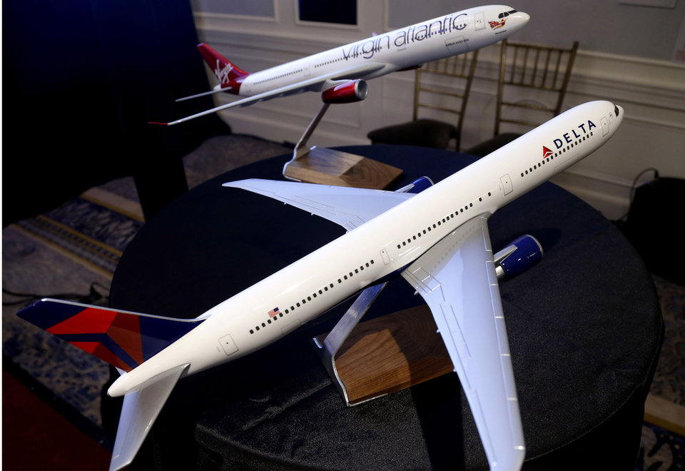 Photo - Model planes bearing the logos of Delta Airlines and Virgin Atlantic are displayed during a news conference in New York, Tuesday, Dec. 11, 2012. Delta Air Lines said it will buy almost half of Virgin Atlantic for $360 million as it tries to catch up to rivals in the lucrative New York-to-London travel market. (AP Photo/Seth Wenig)