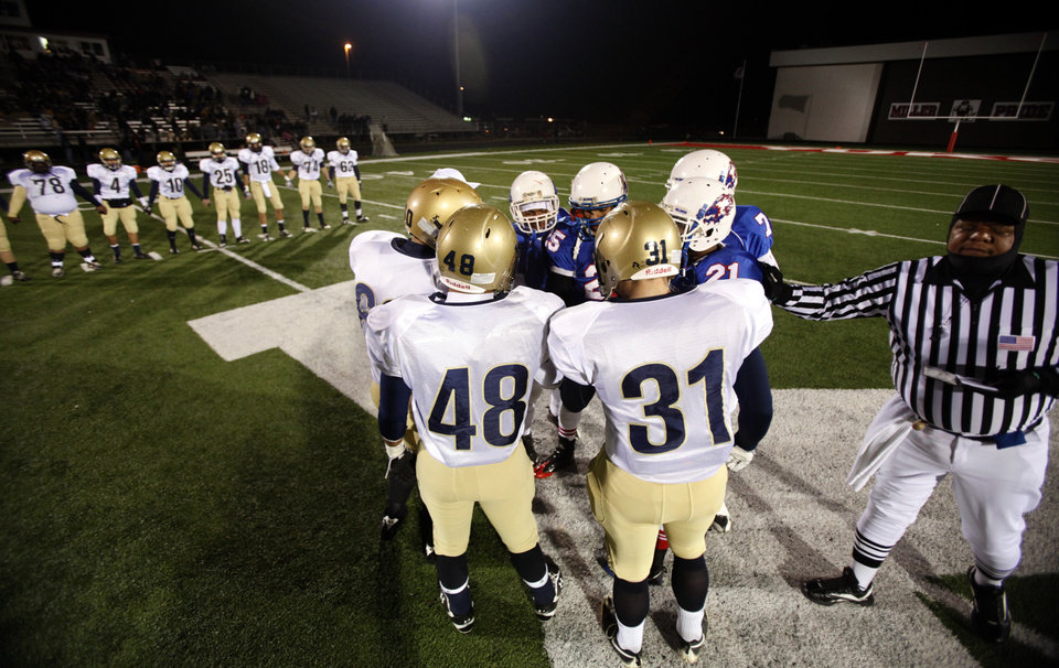 Kingfisher and Millwood huddle up a midfield before the Class 2A State semifinal football game between Millwood High School and Kingfisher High School on Saturday, Dec. 5, 2009, in Yukon, Okla. 