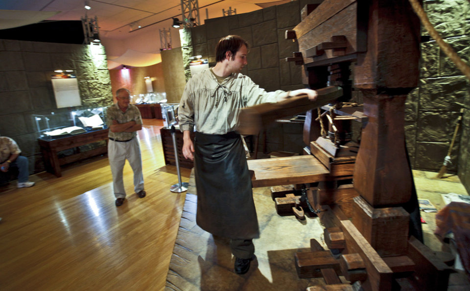 "Andrew Cole demonstrates the operations of a Gutenberg press to visitors of the ""Passages"" exhibit at the Oklahoma City Museum of Art. The collection of biblical artifacts was on display last year. Photos by Chris Landsberger, The Oklahoman Archives"