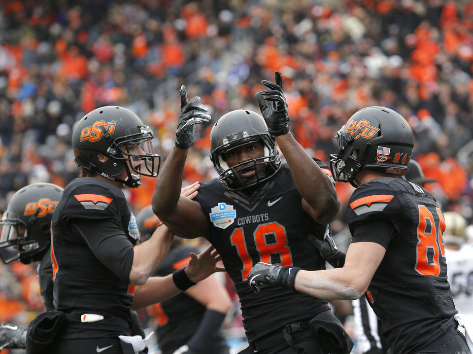 Photo - Oklahoma State's Clint Chelf (10), Blake Jackson (18) and Austin Hays (84) celebrate a Jackson touchdown during the Heart of Dallas Bowl football game between the Oklahoma State University (OSU) and Purdue University at the Cotton Bowl in Dallas,  Tuesday,Jan. 1, 2013. Photo by Sarah Phipps, The Oklahoman