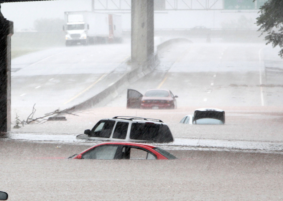 Cars are almost covered in water Monday under a railroad bridge on the Broadway Extension in Oklahoma City. PHOTO By Paul Hellstern, The Oklahoman