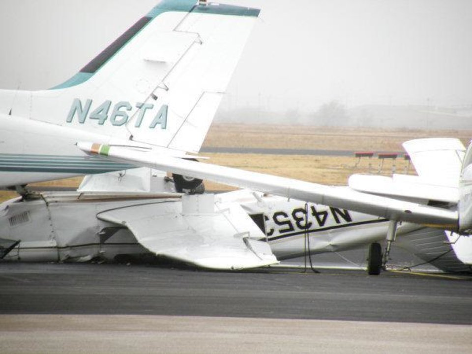 Photo - Two planes damaged in a severe storm Monday night sit on the tarmac at Max Westheimer Airport Tuesday afternoon. Several more planes and a hangar were damaged.  Jacob Green