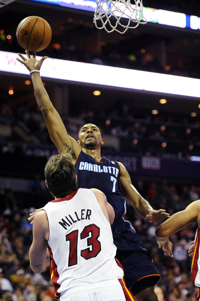 Photo - Charlotte Bobcats' Ramon Sessions (7) drives in on Miami Heat's Mike Miller (13) during the first half of their NBA basketball game, Wednesday, Dec. 26, 2012, in Charlotte. The Heat won 105-92. (AP Photo/The Charlotte Observer, David T. Foster III) MAGS OUT; TV OUT; NEWSPAPER INTERNET ONLY