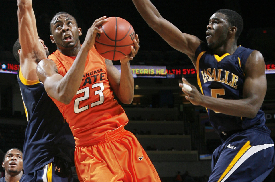 Photo - OSU's James Anderson, center, drives to the hoop between La Salle's Jerrell Williams, left, and Kimmani Barrett during action Monday at the All-College Classic. Oklahoma State is riding a four-game winning streak and won't play again until Dec. 29. Photo by Nate Billings, The Oklahoman