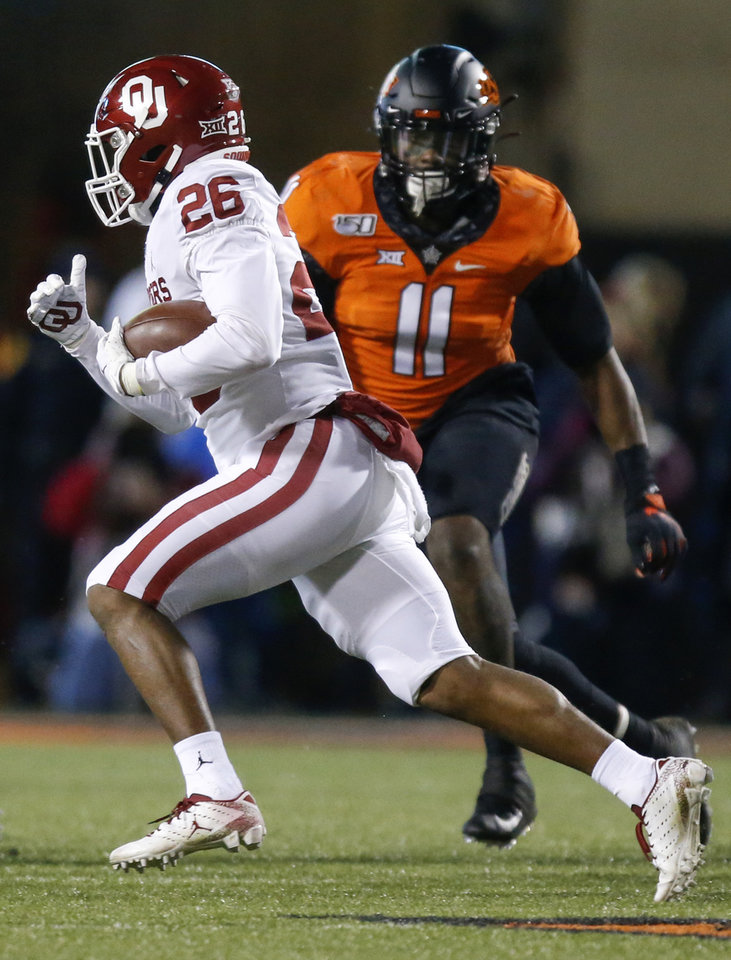 Photo - Oklahoma's Kennedy Brooks (26) carries the ball as Oklahoma State's Amen Ogbongbemiga (11) defends during the Bedlam college football game between the Oklahoma State Cowboys (OSU) and Oklahoma Sooners (OU) at Boone Pickens Stadium in Stillwater, Okla., Saturday, Nov. 30, 2019. [Nate Billings/The Oklahoman]