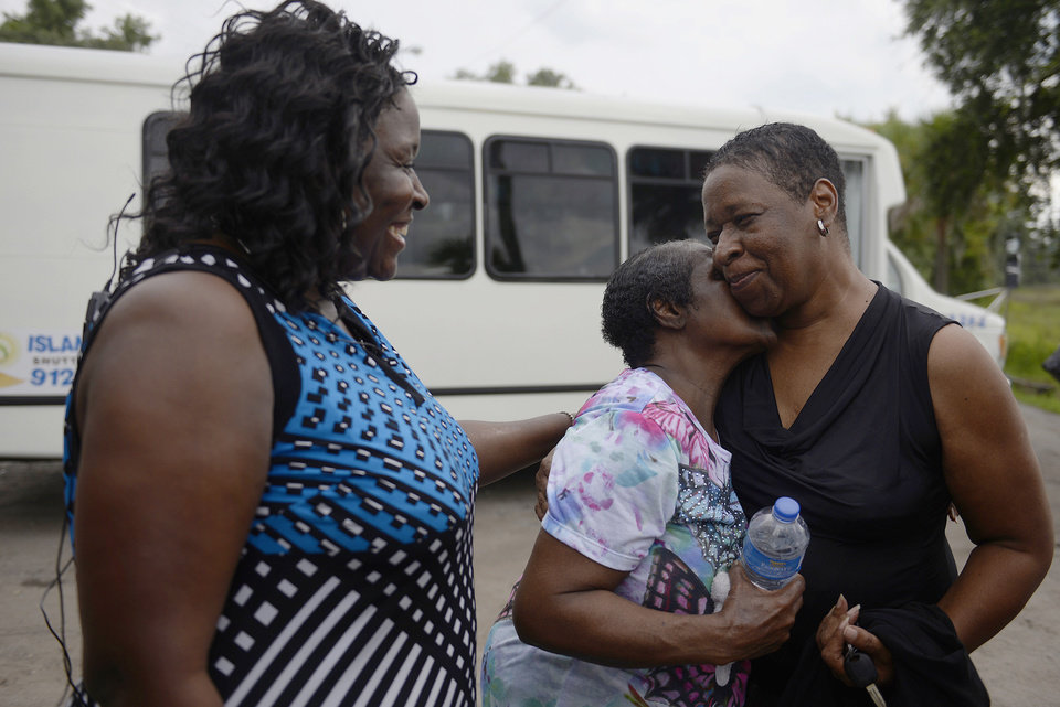 Photo - From left, Tara Sinclair and Gwendolyn Snowden Miller greet Veronica Hayward as she returned to Wilmington Island, Ga. after being evacuated from the Escapade casino boat on Wednesday, July 16, 2014. The boat became grounded on a sandbar between Tybee Island and Hilton Head Island Tuesday evening. Passengers and crew remained on the boat for 16 hours before the U.S. Coast Guard evacuated the boat. (AP Photo/The Morning News, Brittney Lohmiller)