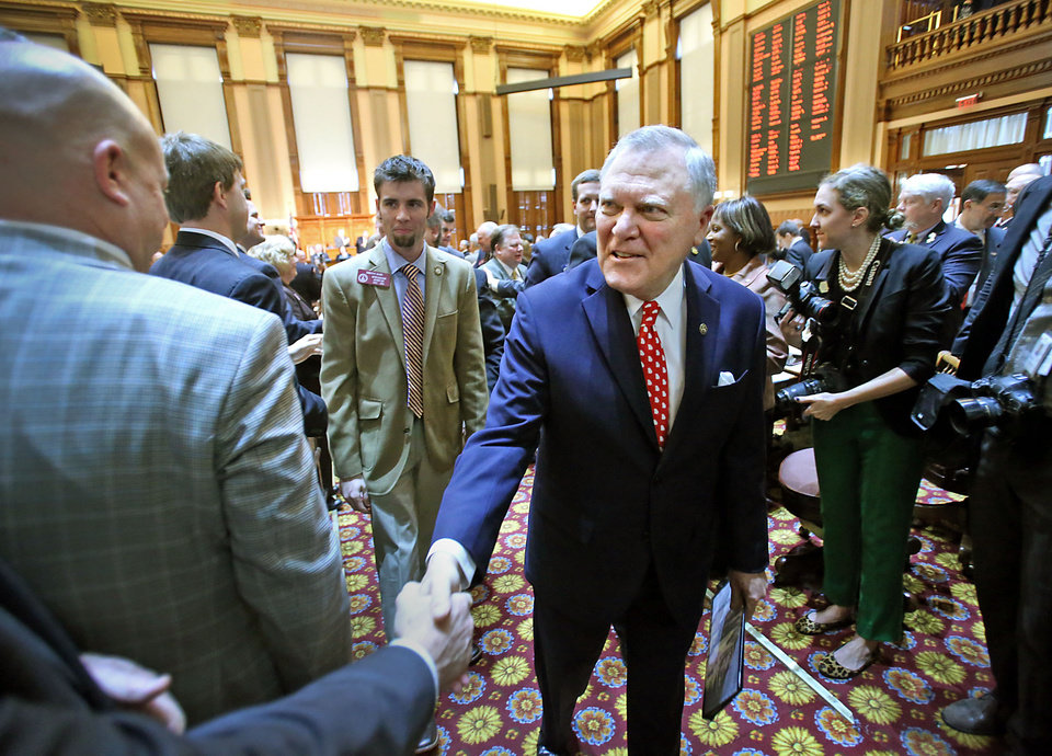 Photo - Georgia Gov. Nathan Deal, center, walks with his escorts as he shakes hands with legislators as he leaves the House Chambers after delivering the State of the State address in the Georgia State Capitol Thursday, Jan. 17, 2013, in Atlanta.  (AP Photo/Atlanta Journal-Constitution, Jason Getz  )  MARIETTA DAILY OUT; GWINNETT DAILY POST OUT; LOCAL TV OUT; WXIA-TV OUT; WGCL-TV OUT