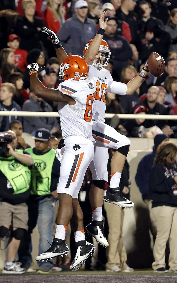 Oklahoma State 's Clint Chelf (10) and Tracy Moore (87) celebrate a Chelf touchdown during the college football game between the Oklahoma State Cowboys (OSU) and the Texas Tech Red Raiders (TTU) at Jones AT&T Stadium in Lubbock, Texas, Saturday, Nov. 2, 2013. Photo by Sarah Phipps, The Oklahoman