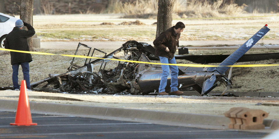 Photo - Federal Aviation Administration investigators look over the wreckage of a medical helicopter that crashed Friday in between the St. Ann Retirement Center and St. Ann Nursing Home in northwest Oklahoma City. Photo By Paul Hellstern, The Oklahoman