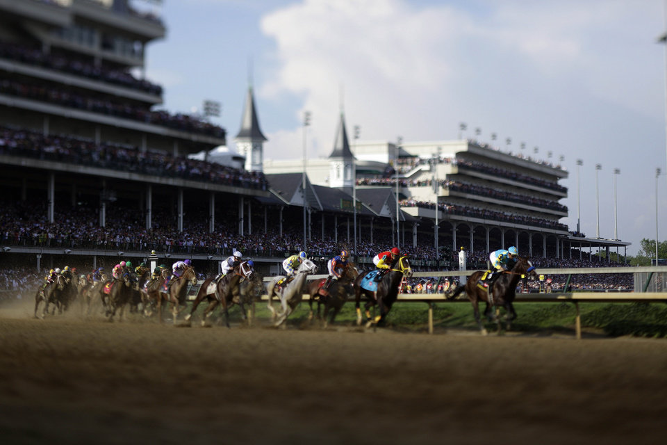 Photo - In a photo taken with a tilt-shift lens, jockey Mike Smith riding Bodemeister leads the field around the first turn in the 138th Kentucky Derby horse race at Churchill Downs Saturday, May 5, 2012, in Louisville, Ky. (AP Photo/Matt Slocum)  ORG XMIT: DBY221